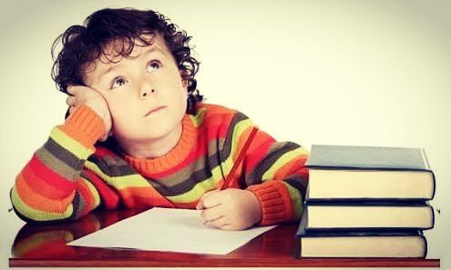 crianca-pensando-em-cima-de-livros